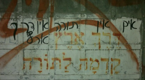"""Another reason why I love living in Israel-- graffiti like this (right next to the Machaneh Yehuda market).  The original graffiti (in red) insists """"Common decency takes precedence over Torah"""" to which another graffiti painter (writing in black) responded """"If there's no Torah, there's no common decency!""""  I'm not a fan of graffiti (the writing of which seems, in fact, to be a contradiction of common decency), but I do adore living in a place where Judaism is so central to our lives that people are even arguing about it on the walls of the city."""