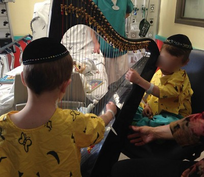 The Gross brothers playing harp with music therapist this week at the Schneider Children's Hospital.