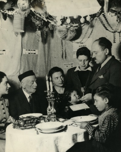 Saba Shlomo as a child in his family's succah, standing to the left of his father making kiddush.