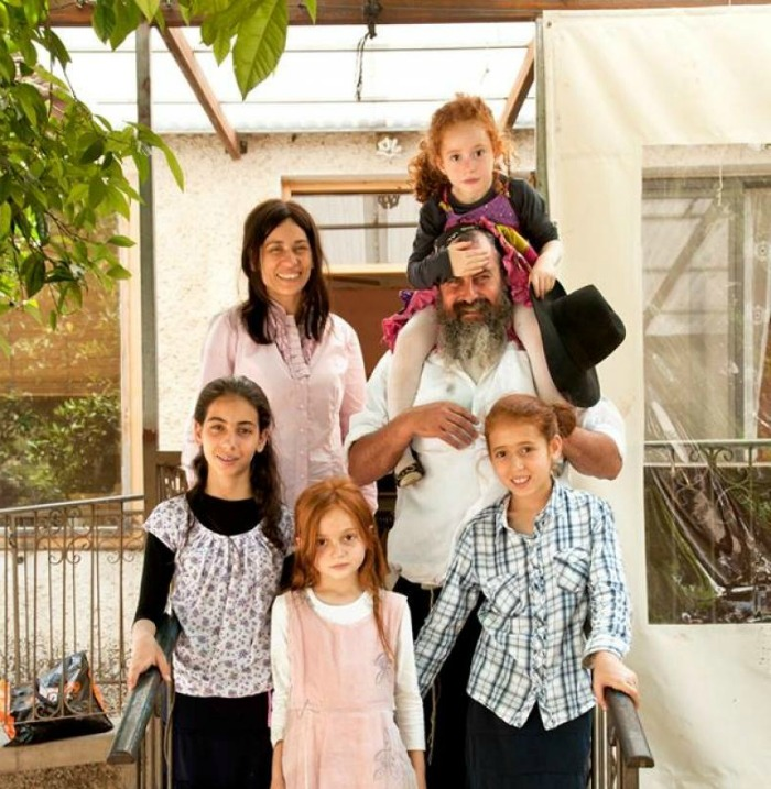 The Vaspis in front of their old home with their 4 daughters.